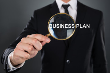 Businessman Showing Business Plan Through Magnifying Glass
