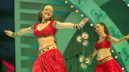 Artist girl dancing on stage in a red national Indian suit