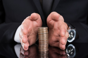 Businessman Protecting Stacked Coins