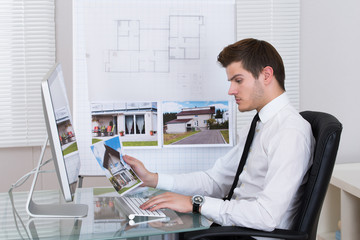 Real Estate Agent Working On Computer