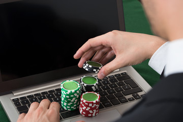 Businessman Using Laptop With Stacked Poker Chips