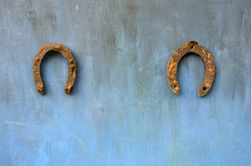 two ancient rusty horseshoe on blue wall
