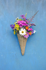 wicker basket with summer flowers on blue wall