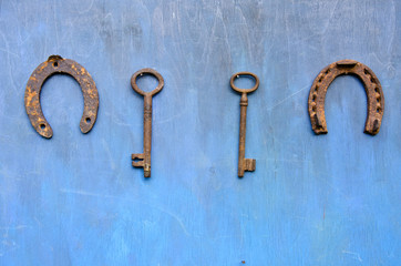 rusty ancient key and horseshoe hang on wooden barn wall