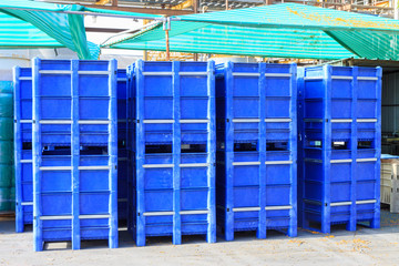 Big blue containers under green tent