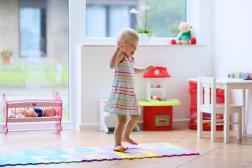 Cute toddler girl dancing at home or kindergarten