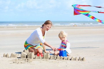 Young mother and child building sand castles on the beach