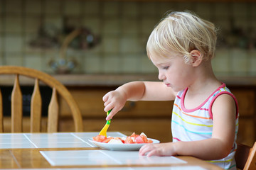 Cute toddler girl eating healthy salad in the kitchen