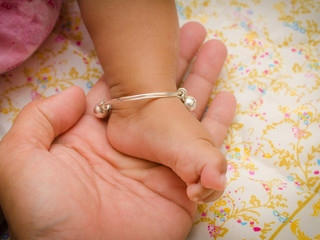 Anklet of newborns in mom's hand