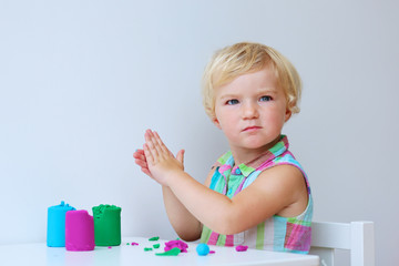Cute preschooler girl playing with colorful compound dough