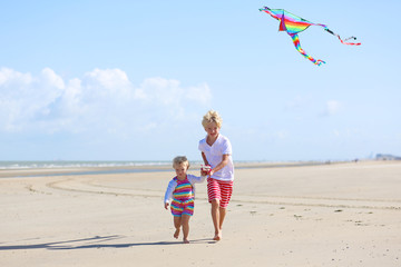 Happy brother and sister playing on the beach flying kite