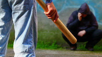 Aggressive teenager with a baseball bat against man with  phone