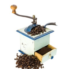 Old coffee grinder and some coffee beans on white background