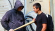 Man with a baseball bat talking with teenager at outdoor