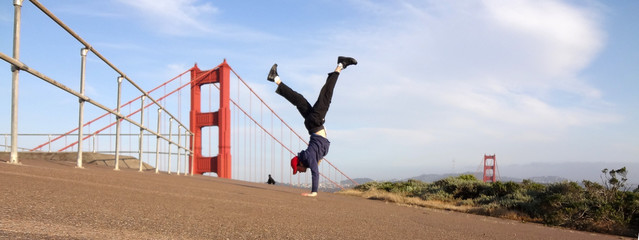 Man wearing hat, hoodie, long pants and shoes Handstands in fron