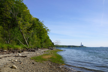 Rocky beach lined with trees on Cousins Island with Large Gas Po