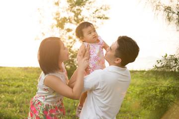 Asian family playing at park