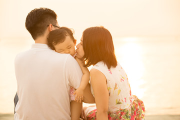 Lovely Asian family at outdoor beach