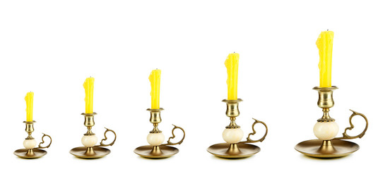 Evolution concept.Old candle holders with candle isolated