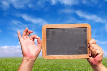 Hand zeigt OK Symbol und hält leere Tafel