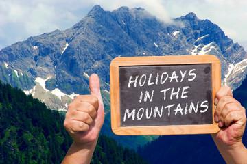 Hände halten Tafel mit Text: Holidays in the Mountains