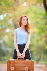 Happy redhead girl with suitcase in the autumn park.