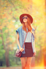 Redhead girl in sunglasses and hat in the autumn park.