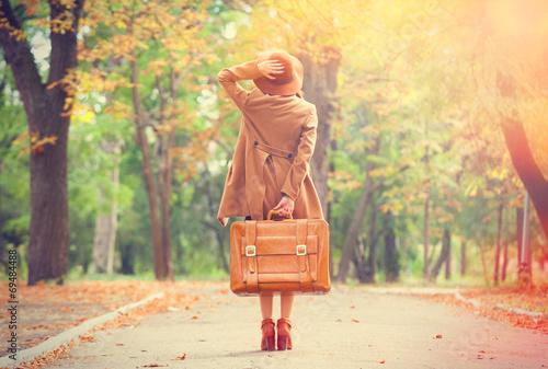 Leinwanddruck Bild Redhead girl with suitcase in the autumn park.