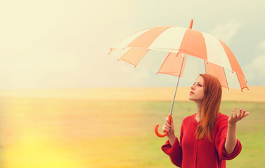 Redhead girl with umbrella at meadow