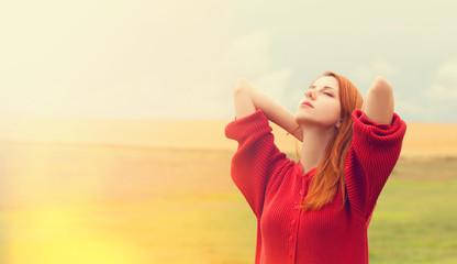 Redhead girl at meadow near wheat field