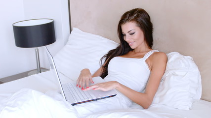 Beautiful Woman Working In Bed On A Laptop Computer