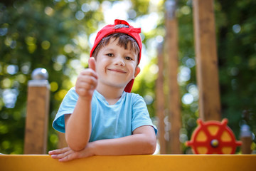 Little boy thumb up outdoor