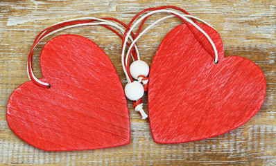 Two red wooden hearts on wooden surface