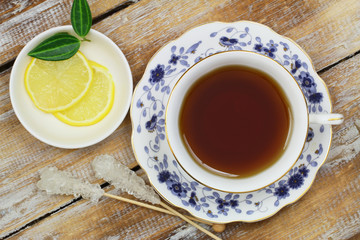 Black tea in vintage cup and lemon on wooden surface