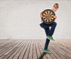 young man holding a dartboard on a room
