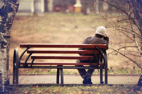 Leinwanddruck Bild lonely man on the bench autumn, winter