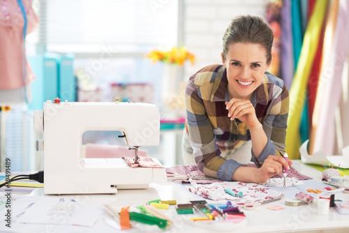 Leinwanddruck Bild Portrait of smiling tailor near sewing machine