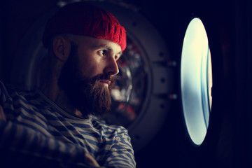 man looking through a porthole of a ship