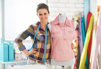 Portrait of happy tailor woman near mannequin