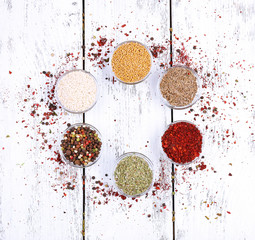 Spices in glass round bowls on wooden background