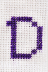 Handmade embroidered letter on white fabric background