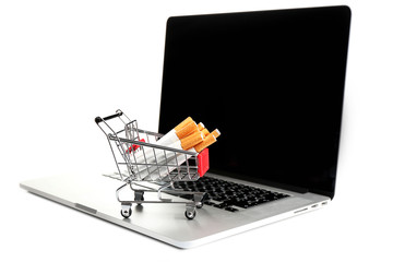 Shopping cart with cigarettes on laptop isolated on white