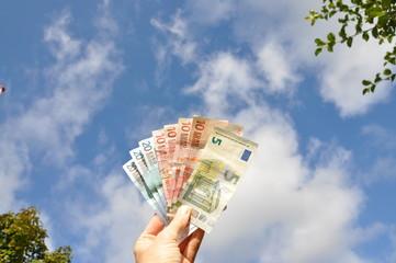 Hand holding money in the sunshine