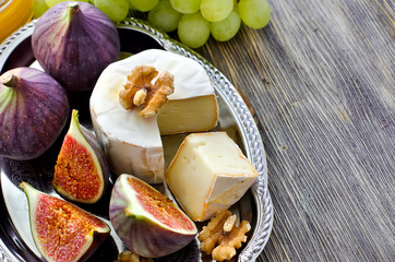Snack with brie, figs and grapes on a tray copy space