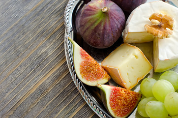 Brie, figs and grapes on a tray copy space