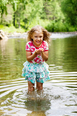 Adorable   girl  in   river on sunny   day