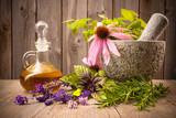 Healing herbs with mortar and bottle of essential oil