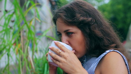 Happy woman drinking beverage in the street cafe and relax