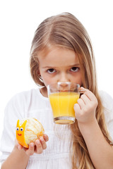 Little girl with fresh orange juice holding snail made of orange