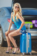 A woman with a suitcase near the car.